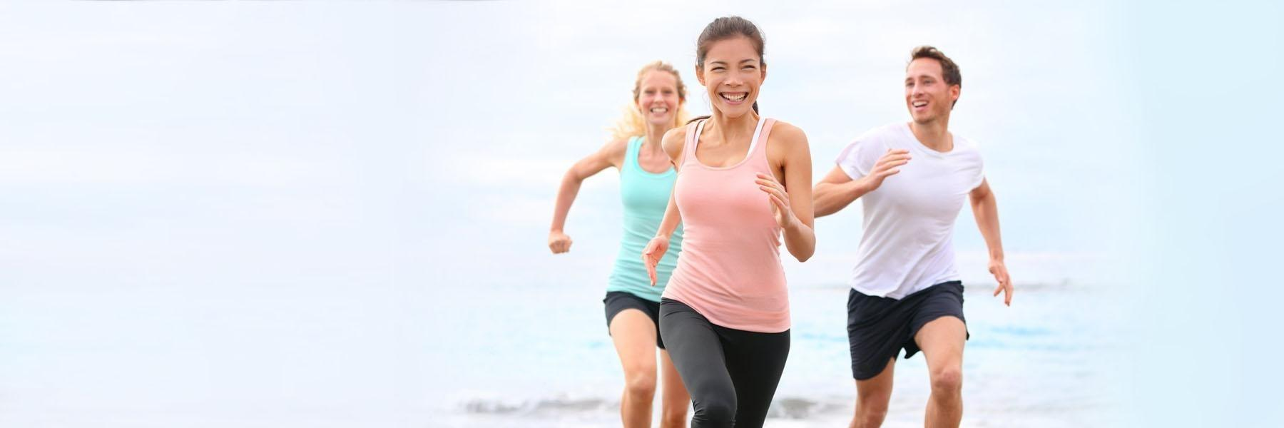 Two women and man running on beach | Dentist Paddington NSW